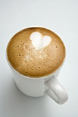 Cup of cappuccino with heart in milk froth