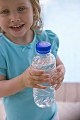 Small girl holding bottle of water