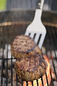 Beef medallions on a barbecue with spatula