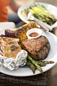 Grilled beef steak with baked potato, corn on the cob, asparagus