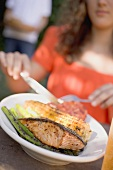 Woman eating grilled salmon with corn on the cob & vegetables