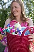 Frau hält Korb mit Deko fürs Gartenfest