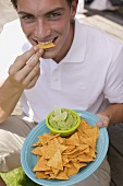 Young man eating tortilla chips with guacamole