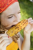 Woman eating grilled corn on the cob
