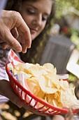 Hand greift nach Chips im Plastikkorb, Frau im Hintergrund