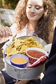 Woman reaching for tortilla chips with two dips in bowl