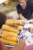 Man serving grilled corn on the cob on 4th of July (USA)