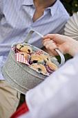 Hand hält Dose mit Heidelbeermuffins, Mann im Hintergrund