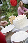 Hand holding piece of coconut cake on server (4th of July, USA)