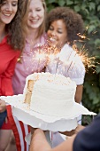 Man serving coconut cake with sparklers (4th of July, USA)
