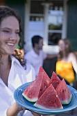 Frau serviert Wassermelonenstücke, Paar im Hintergrund
