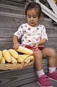 Small girl on wooden steps taking cob of corn from basket