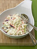 Coleslaw (cabbage salad, USA) in white bowl with cutlery