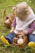 Small girl with baskets of fresh mushrooms in woodland glade