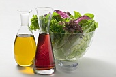 Oil and vinegar in carafes in front of salad bowl