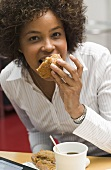 Woman eating muffin in office