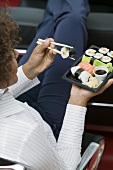 Woman eating sushi in office