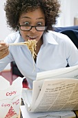 Woman in office eating Asian noodle dish & reading newspaper