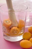 Making a cocktail with kumquats (crushing kumquats in a glass)