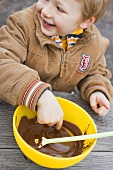 Child tasting chocolate sauce out of bowl