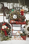 Christmas decorations on garden chair in snow