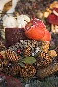 Weihnachtsdeko mit Zapfen, roten Äpfeln und Kerze