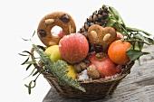 Lebkuchen mit Obst, Nüssen und Zapfen im Korb