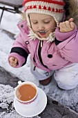 Small girl drinking cocoa from a spoon (out of doors)