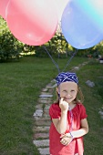 Small girl with balloons in garden