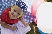 Small girl holding balloons in garden on the 4th of July