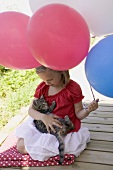 Small girl holding cat and balloons (4th of July, USA)