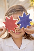Small girl holding two star cookies in front of her eyes