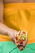 Woman holding a taco filled with beef, salad and cheese
