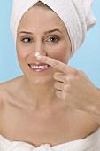 Frau tupft Gesichtscreme auf ihre Nase