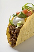 Taco filled with mince, lettuce, avocado and sour cream