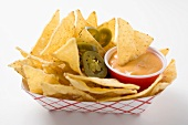 Nachos with chilli rings and dip in cardboard container