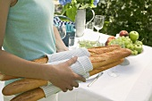 Woman carrying baguettes to table laid out of doors