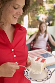 Woman eating a piece of cake on the 4th of July (USA)