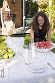 Woman carrying pieces of watermelon to table laid in garden