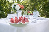 Watermelon, fruit and wine on table laid in garden