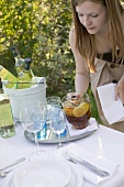 Woman putting a jug of iced tea on table laid in garden