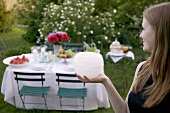 Woman holding windlight in front of table laid in garden