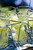 Glasses of water with green grapes in a glass carrier