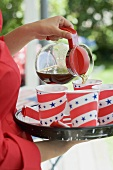 Woman pouring coffee into paper cup (4th of July, USA)