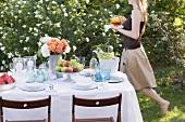 Frau bringt Eistee zu gedecktem Tisch im Garten