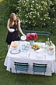 Woman putting plates on table laid in garden