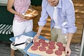 Man preparing burgers for grilling, woman bringing buns