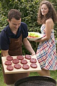 Man holding raw burgers over barbecue, woman serving salad