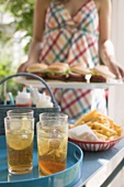 Iced tea and chips on table, woman serving hamburgers