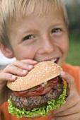 Small boy eating hamburger